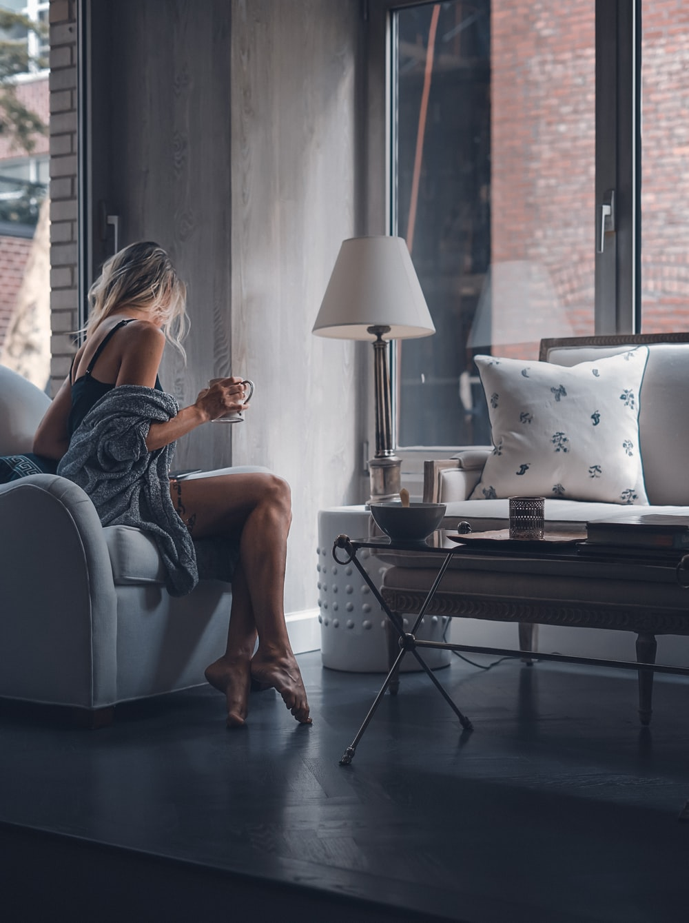 woman sitting on gray sofa chair holding mug