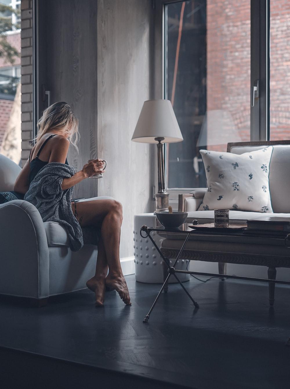 woman sitting on gray sofa chair holding mug