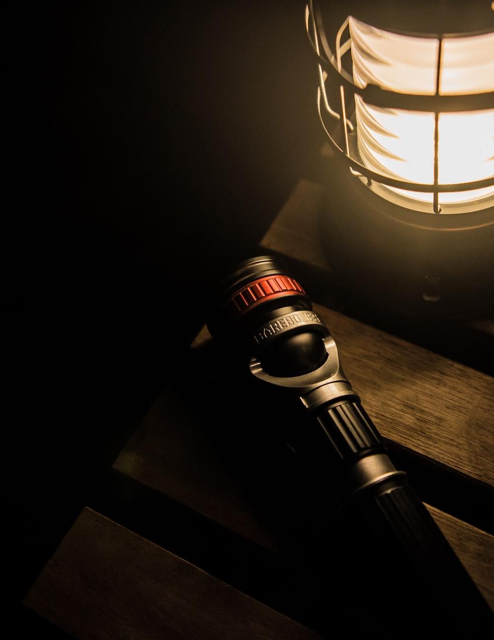 black flashlight beside lantern