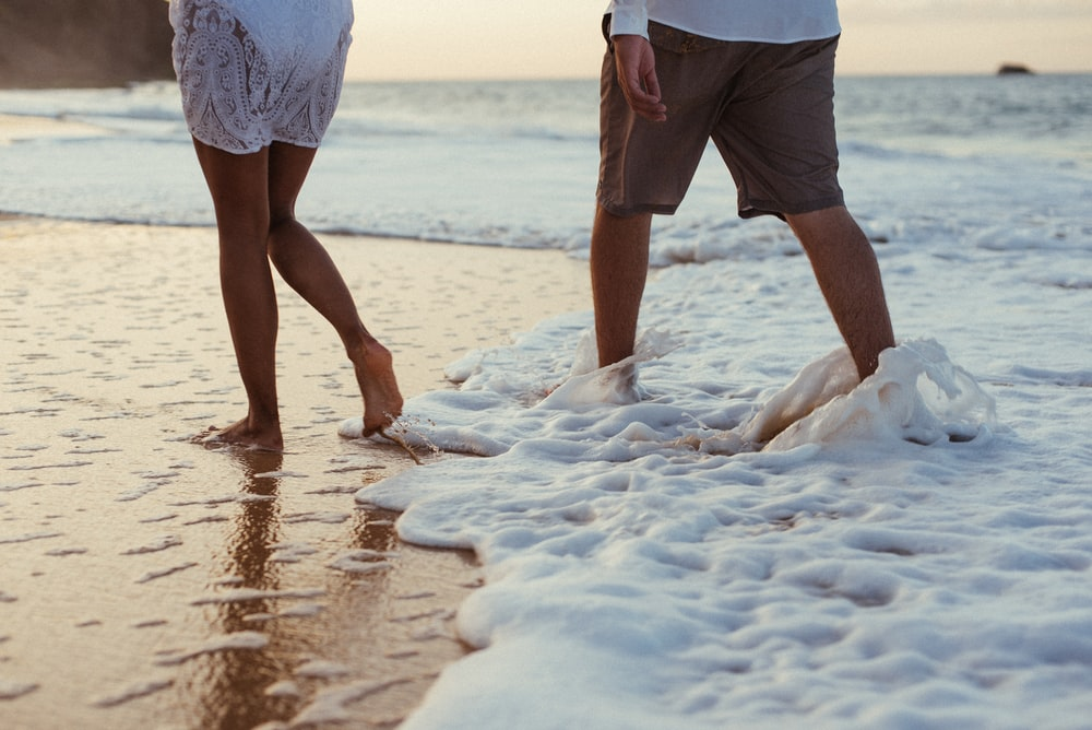 two person walking on shore
