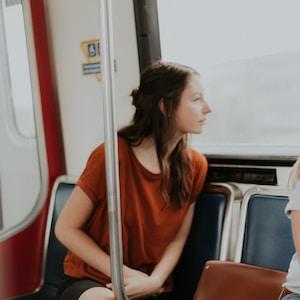 woman sitting on gang chair beside window