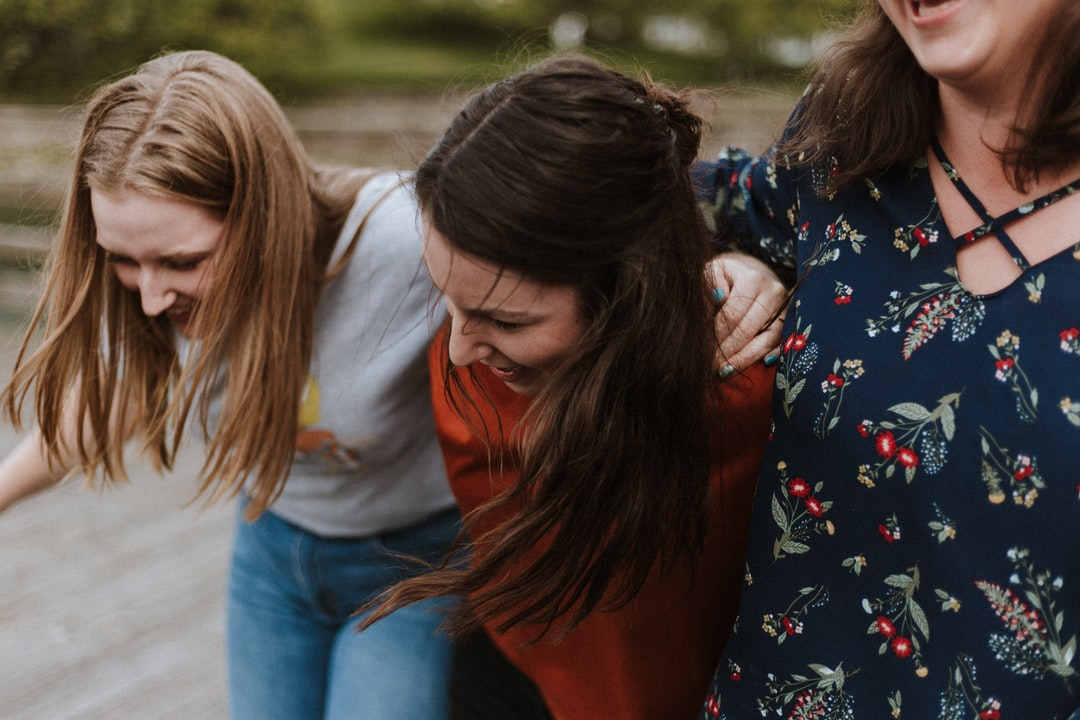 All about staying connected with your friends in your 30s - what is friendship like in your 30s and top tips for how to stay connected. 3 women holding each other and laughing.