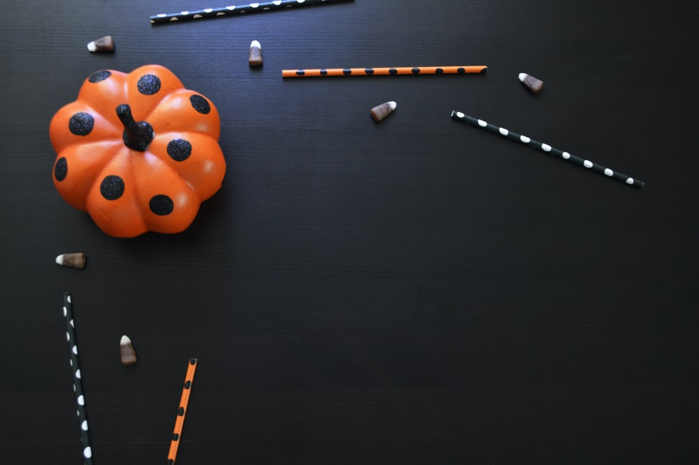 orange and black polka-dot pumpkin toy on black table