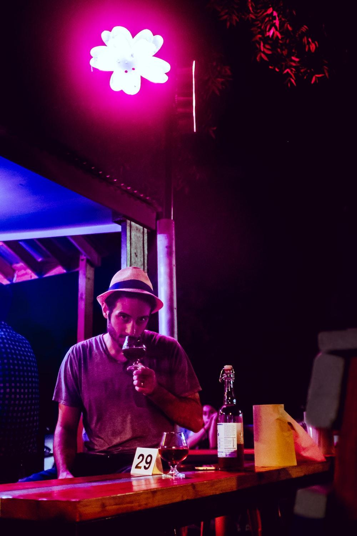 man wearing grey shirt holding wine glass