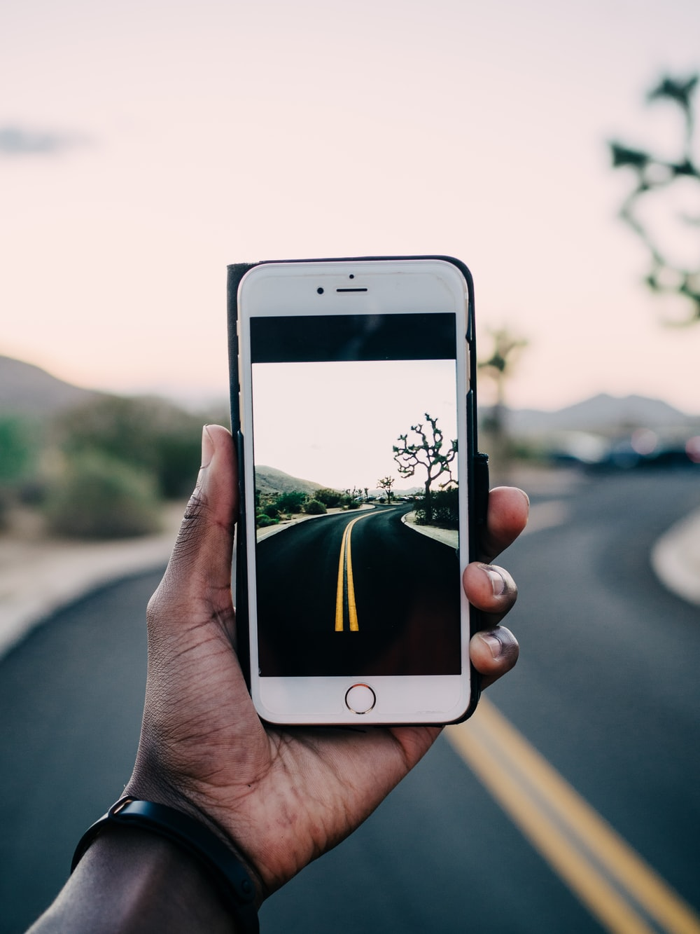 person using gold iPhone 6 capturing road