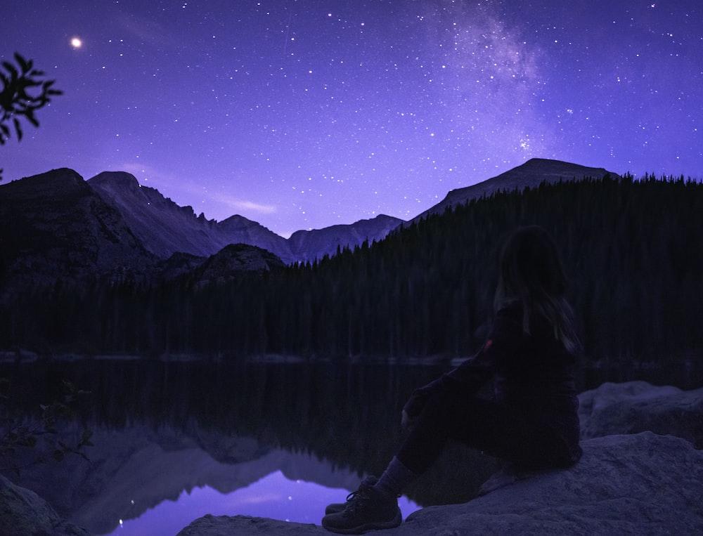 woman sitting on rock near lake facing mountaing