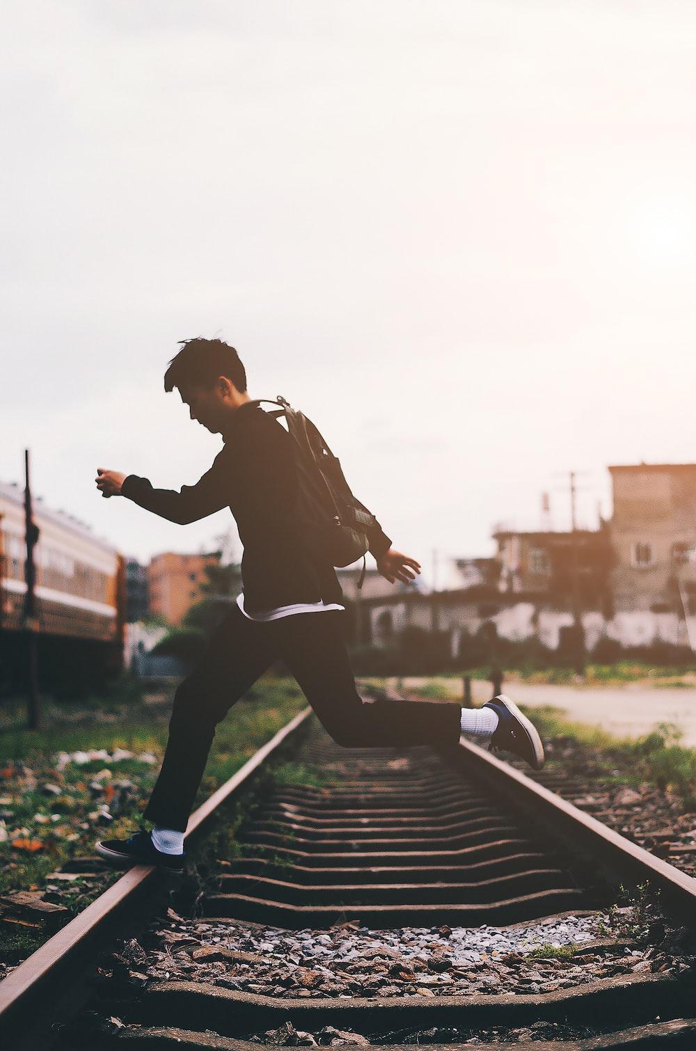 man crossing train track