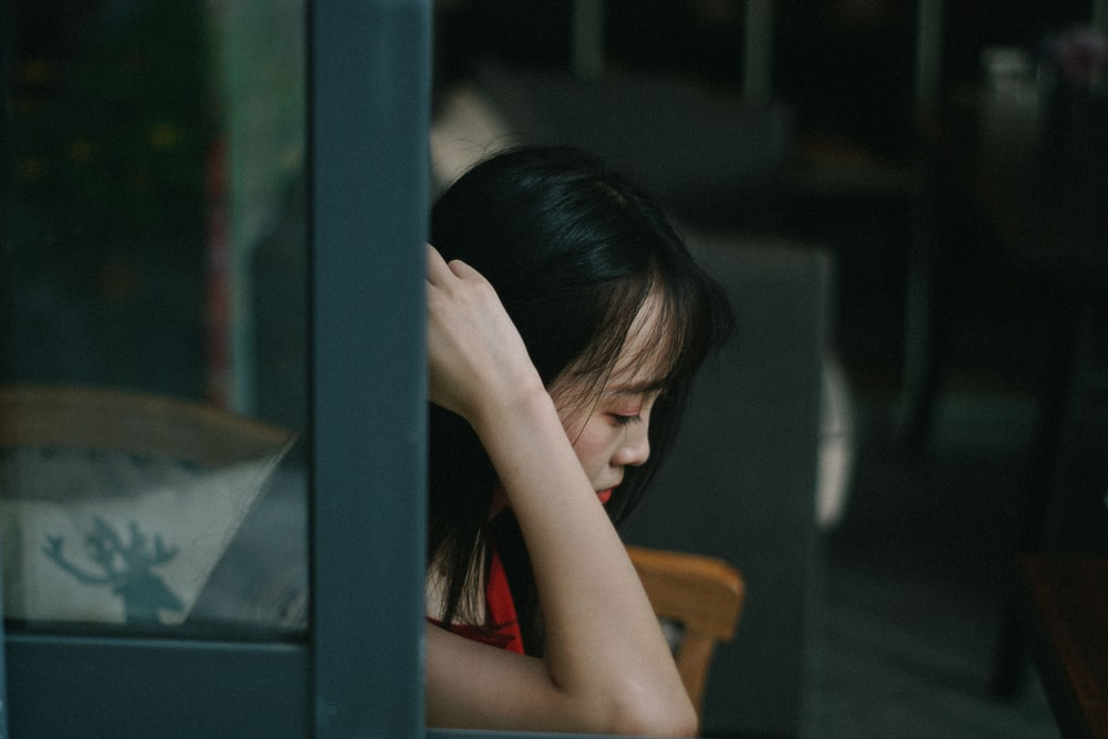 woman sitting down with hand near hair, bullying fisik, bullying tubuh, komentar jelek terhadap tubuh, definisi body shaming