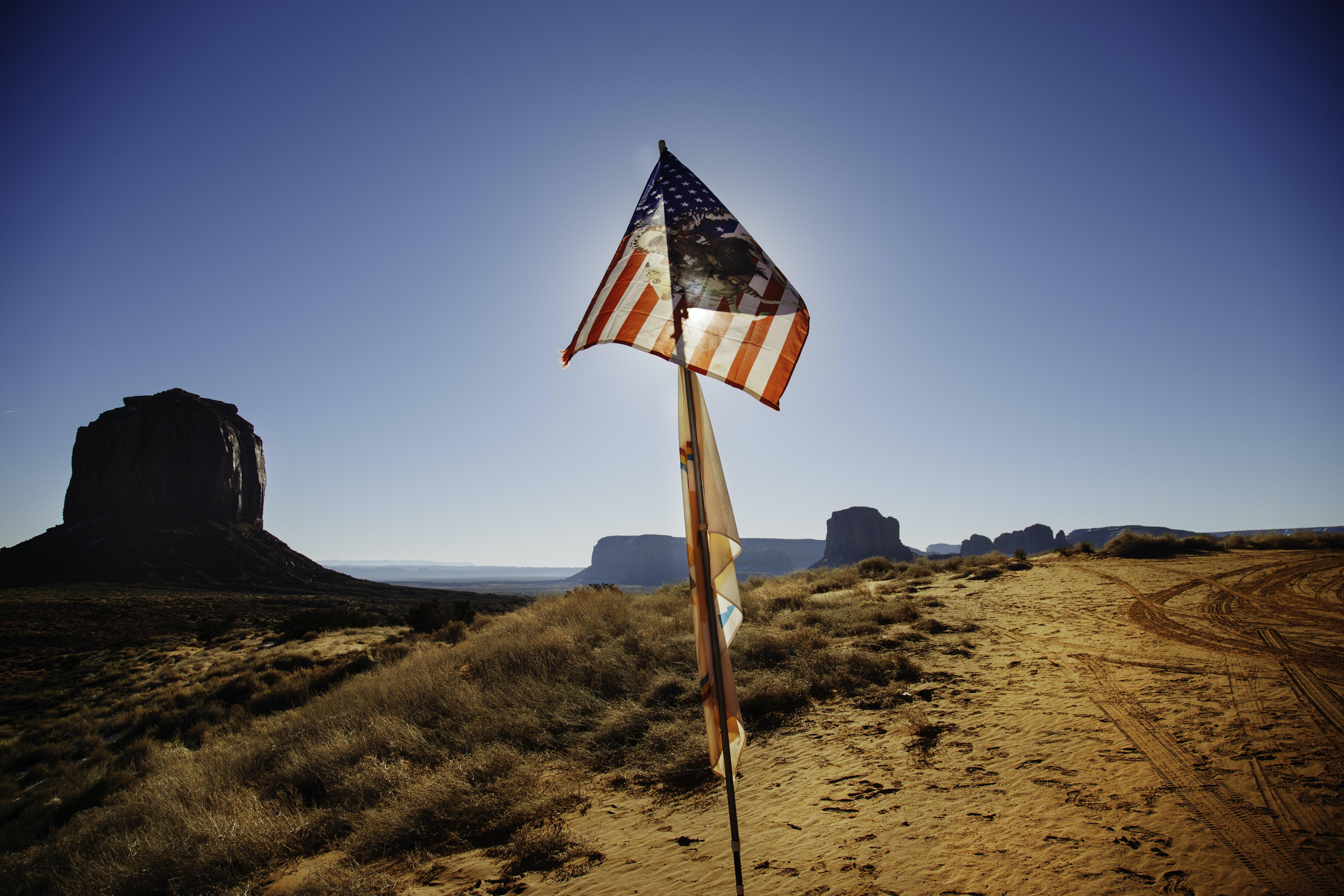 USA flag waving over brown sand