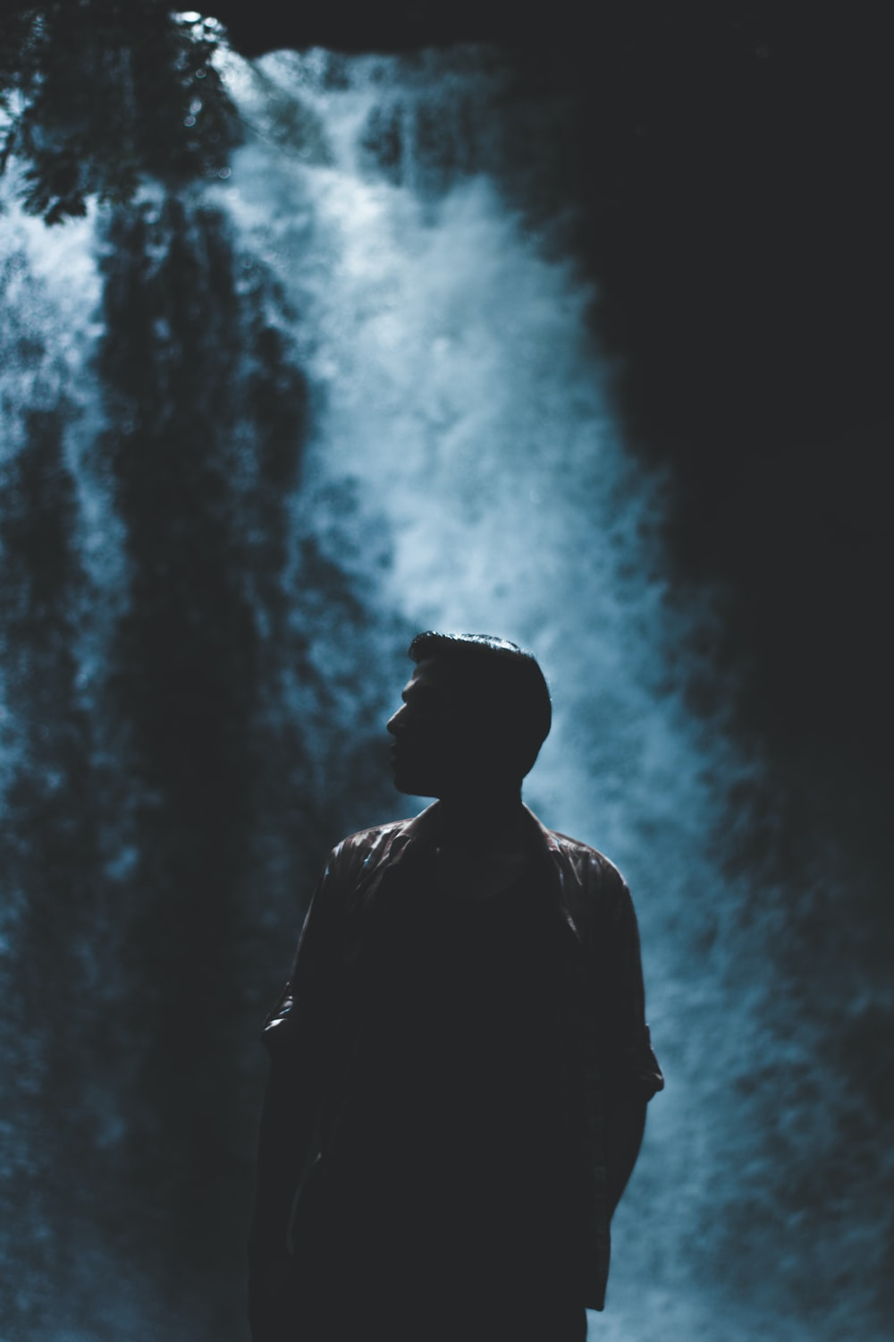 silhouette of man with rushing waterfalls on background