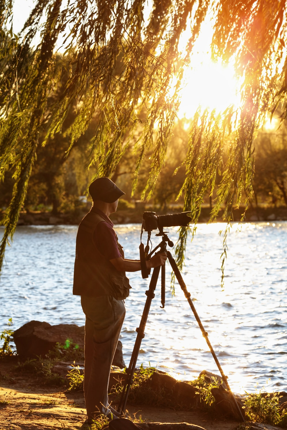 man standing beside DSLR camera with stand near body of water during sunset