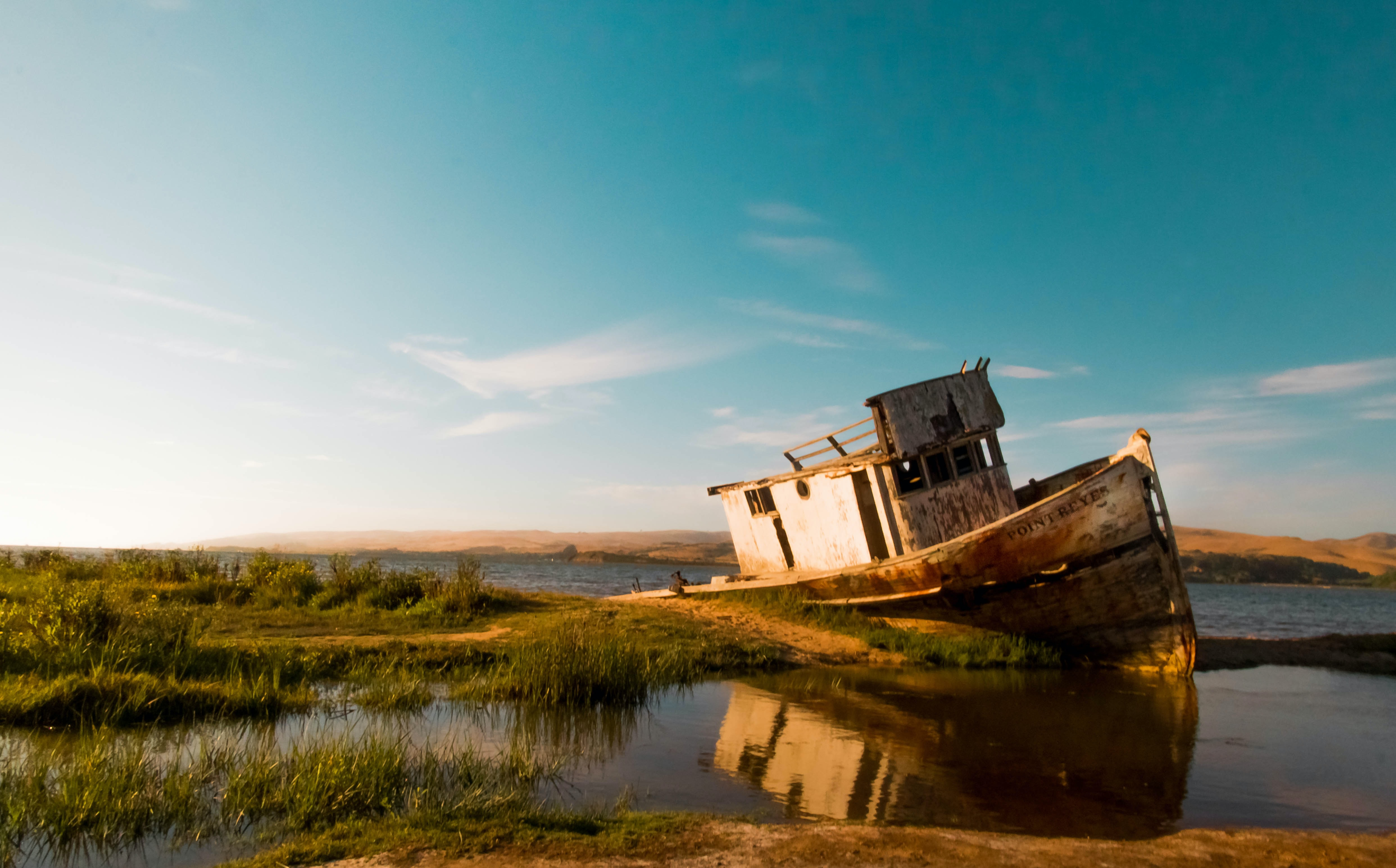abandoned boat on body of water