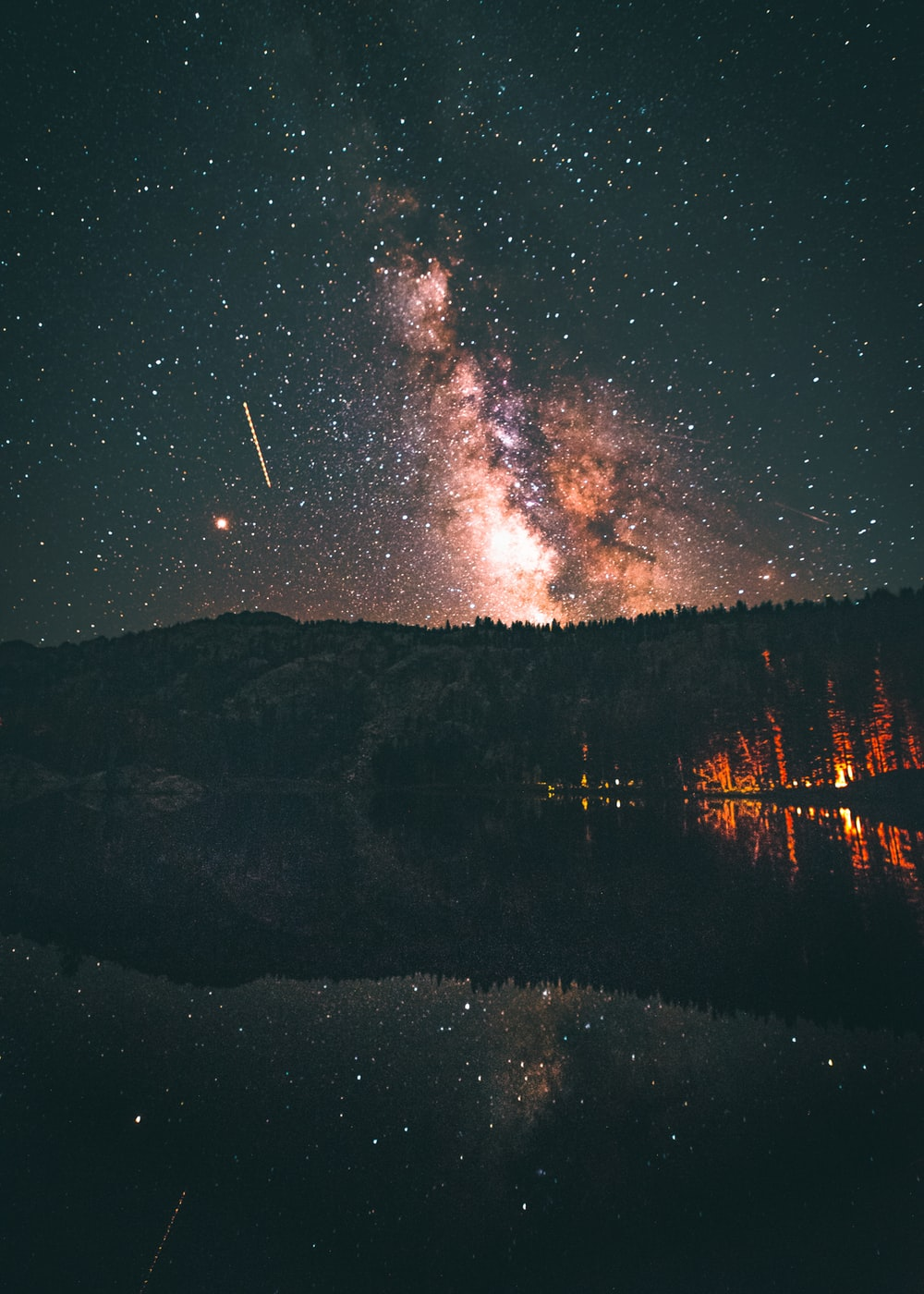 sky phenomenon above pine trees near body of water