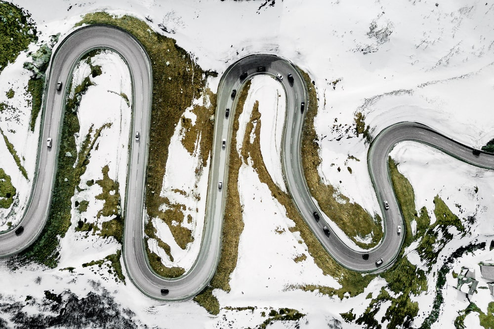 aerial photography of vehicles on road surrounded with snow during daytime