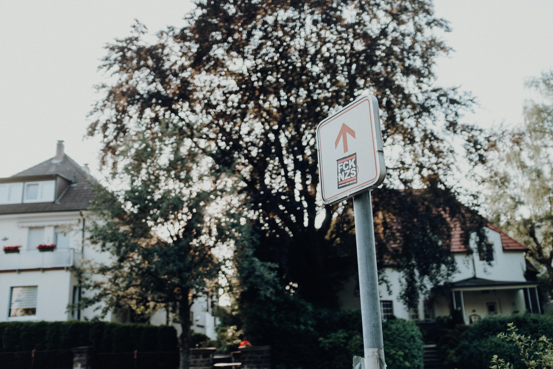 arrow up street sign near tree