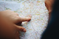person pointing paris on map