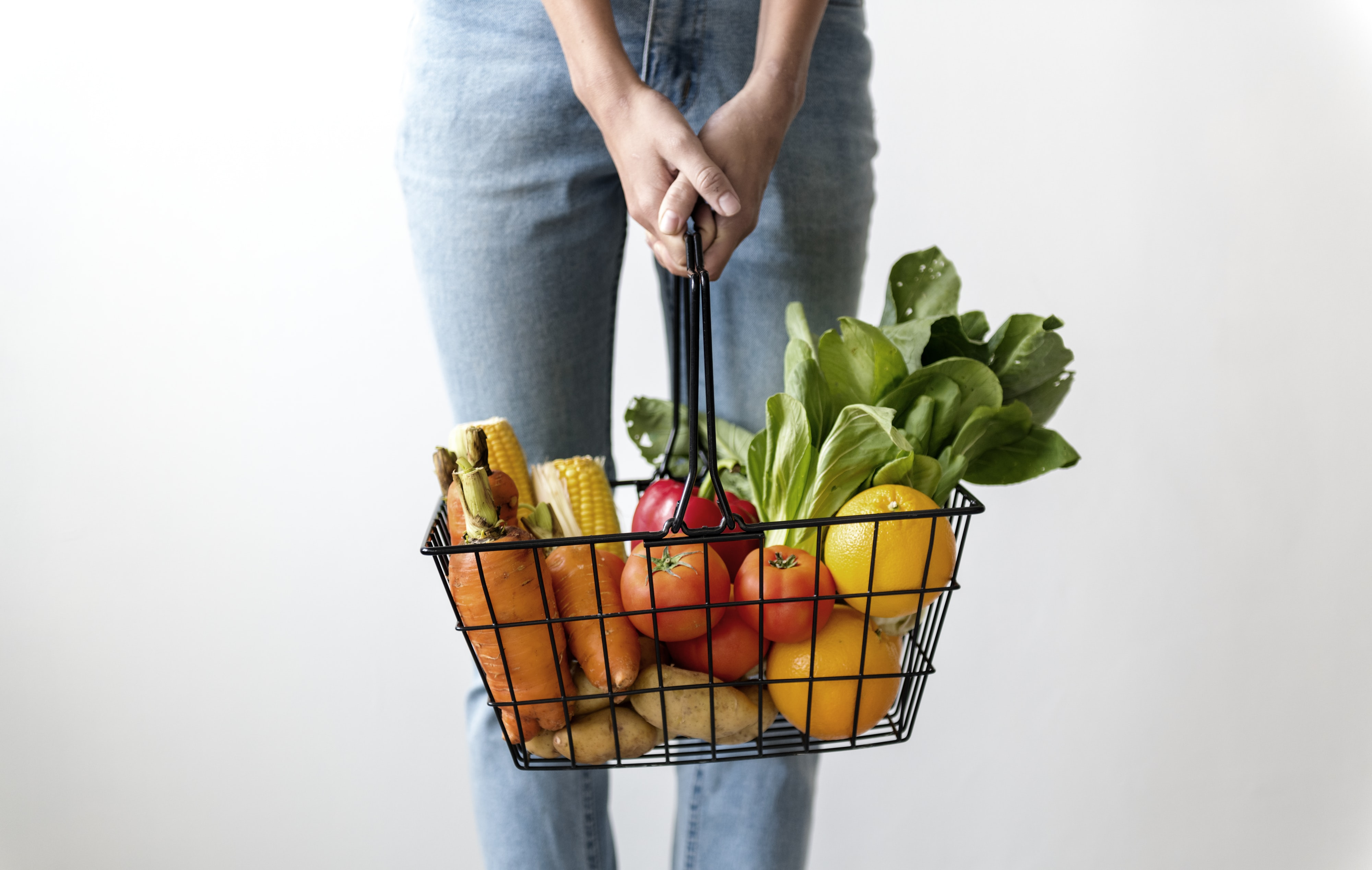 person holding basket filled with vegetables
