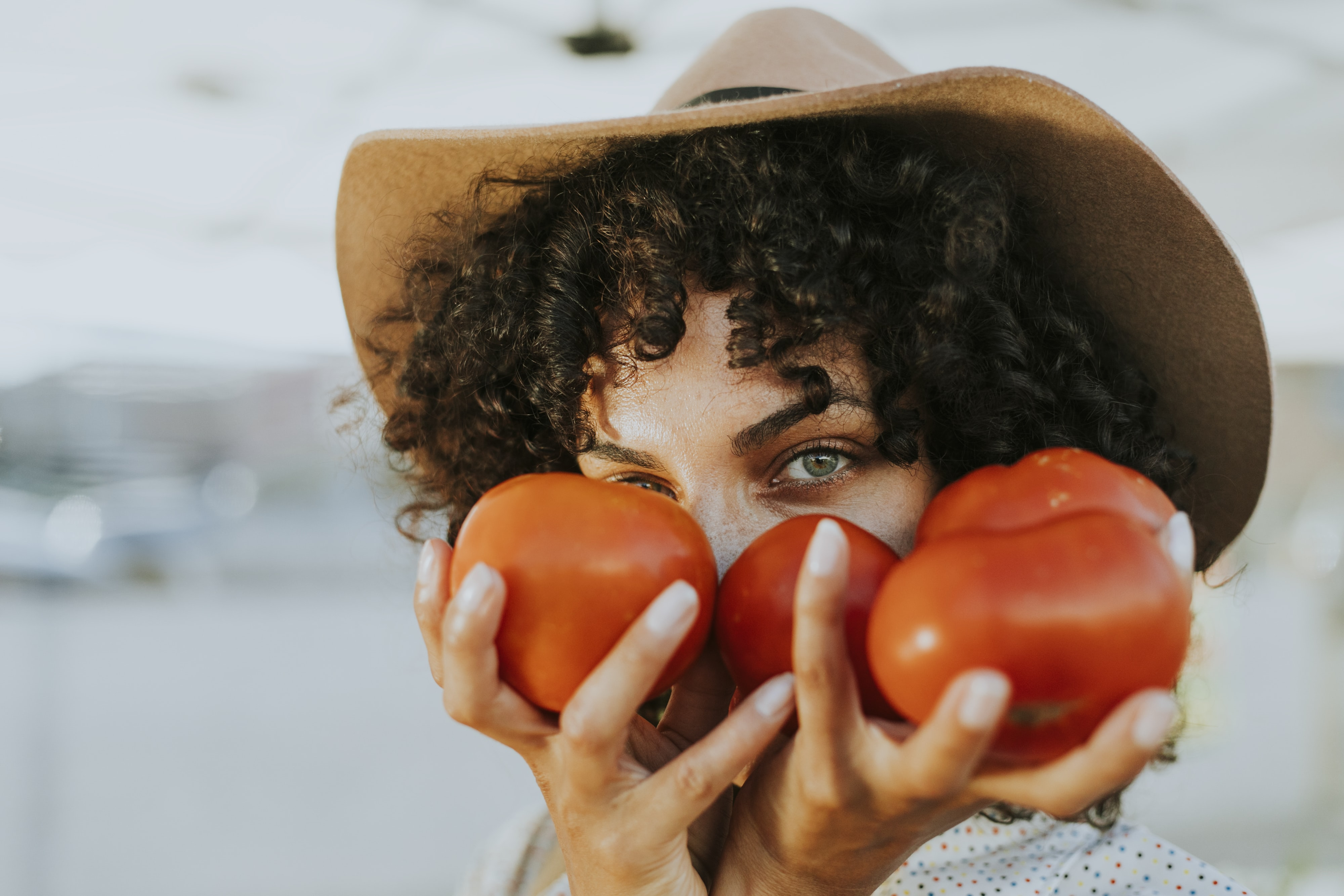person holding red tomatoes