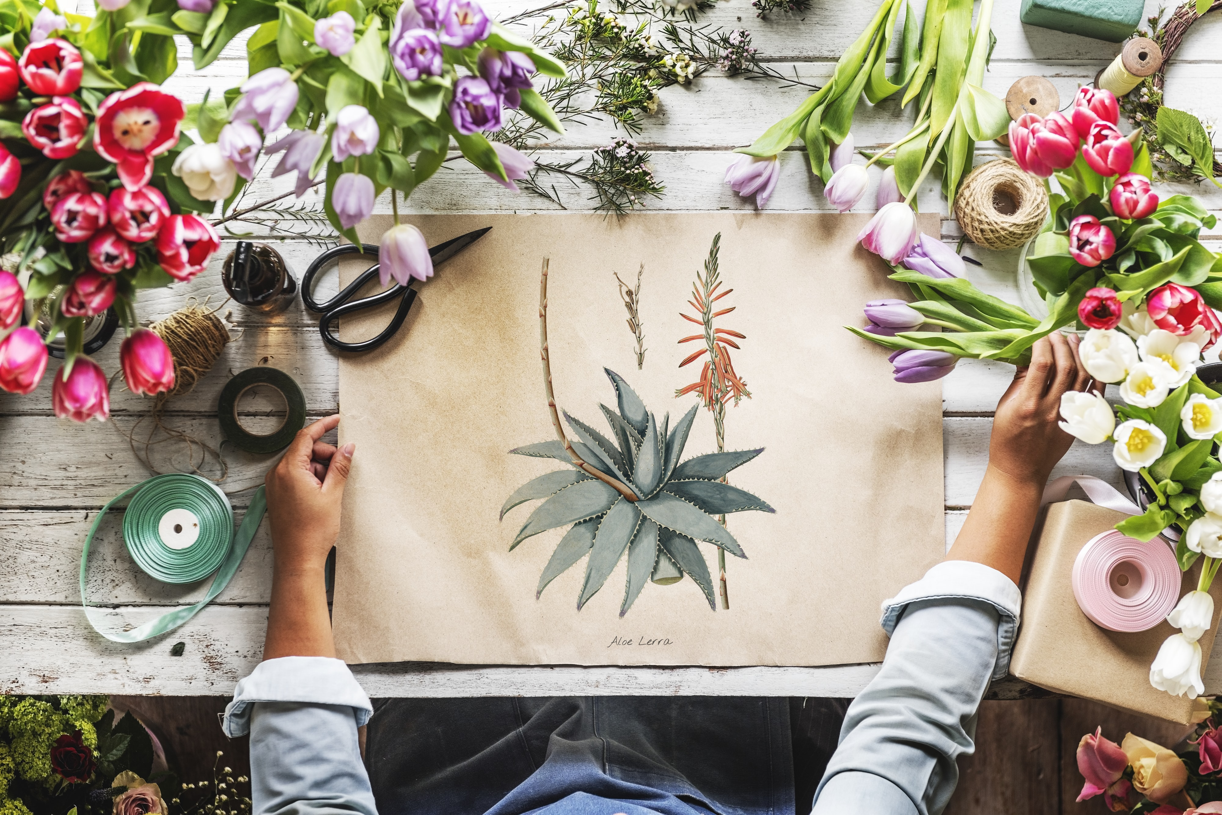 person in gray top painting flowers