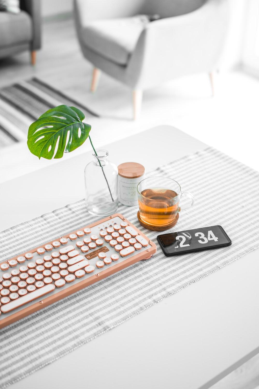 brown computer keyboard beside glass mug