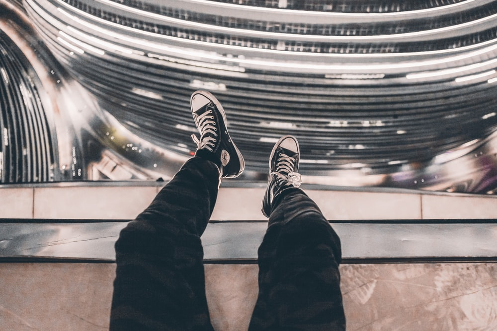 person taking photo of black Converse sneakers