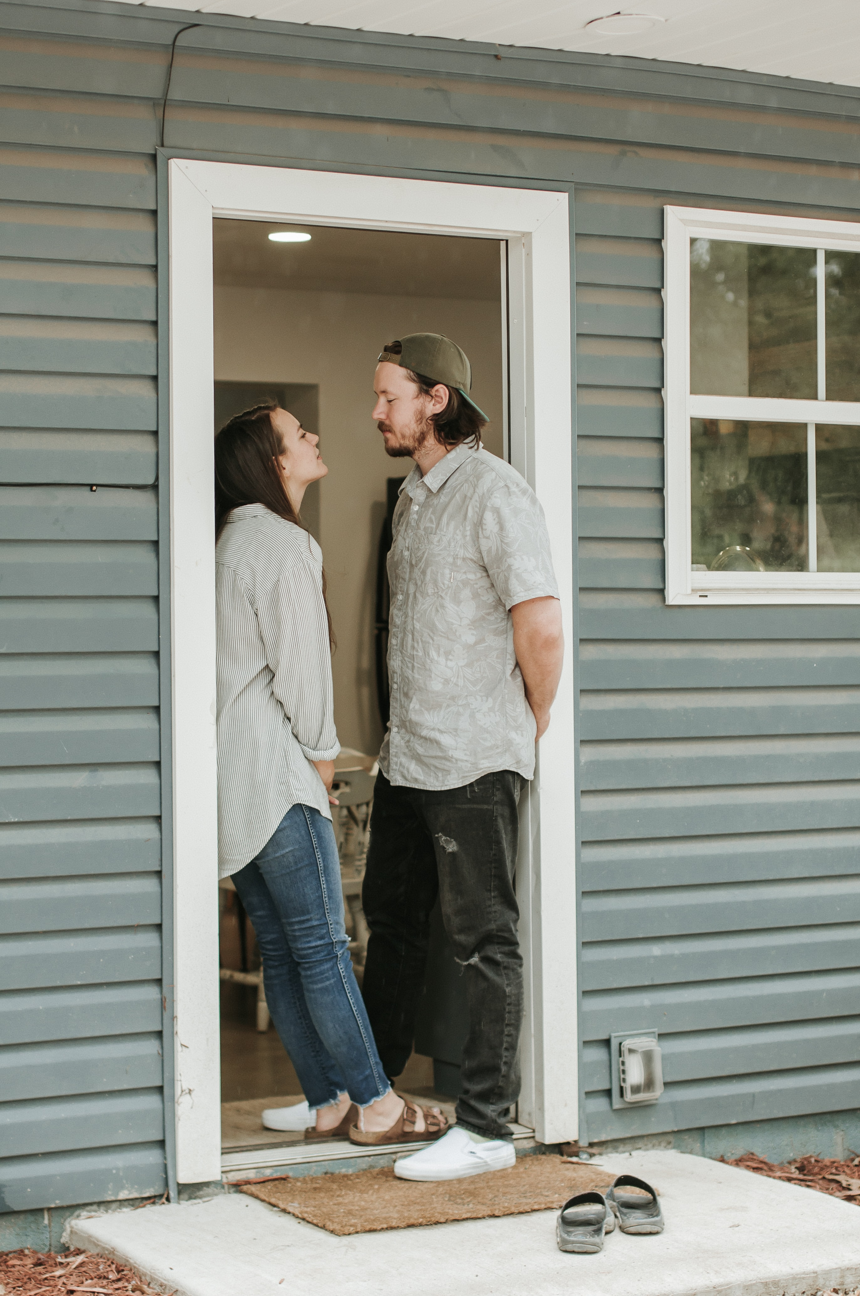 man and woman facing each other on door