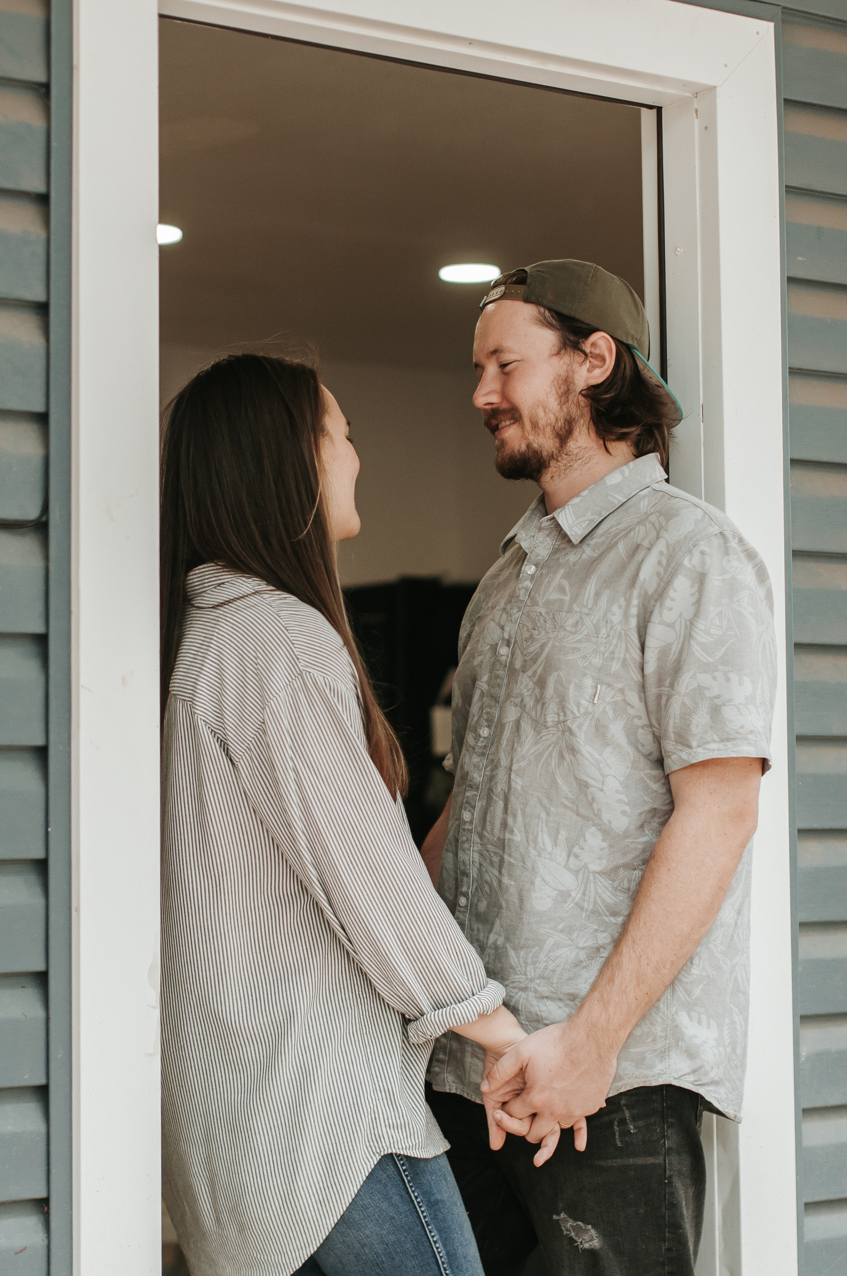 man and woman standing on doorway holding hands