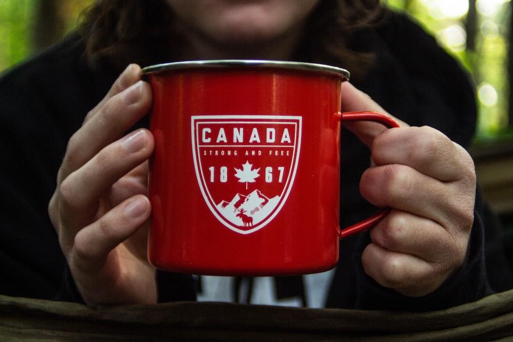 person holding red metal mug