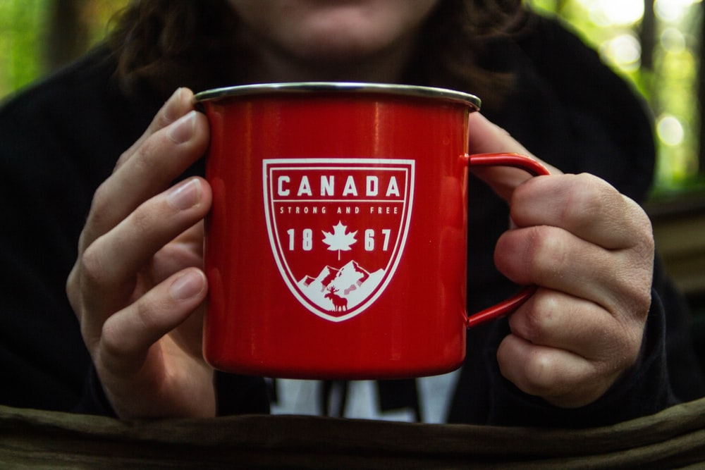 person holding red metal mug