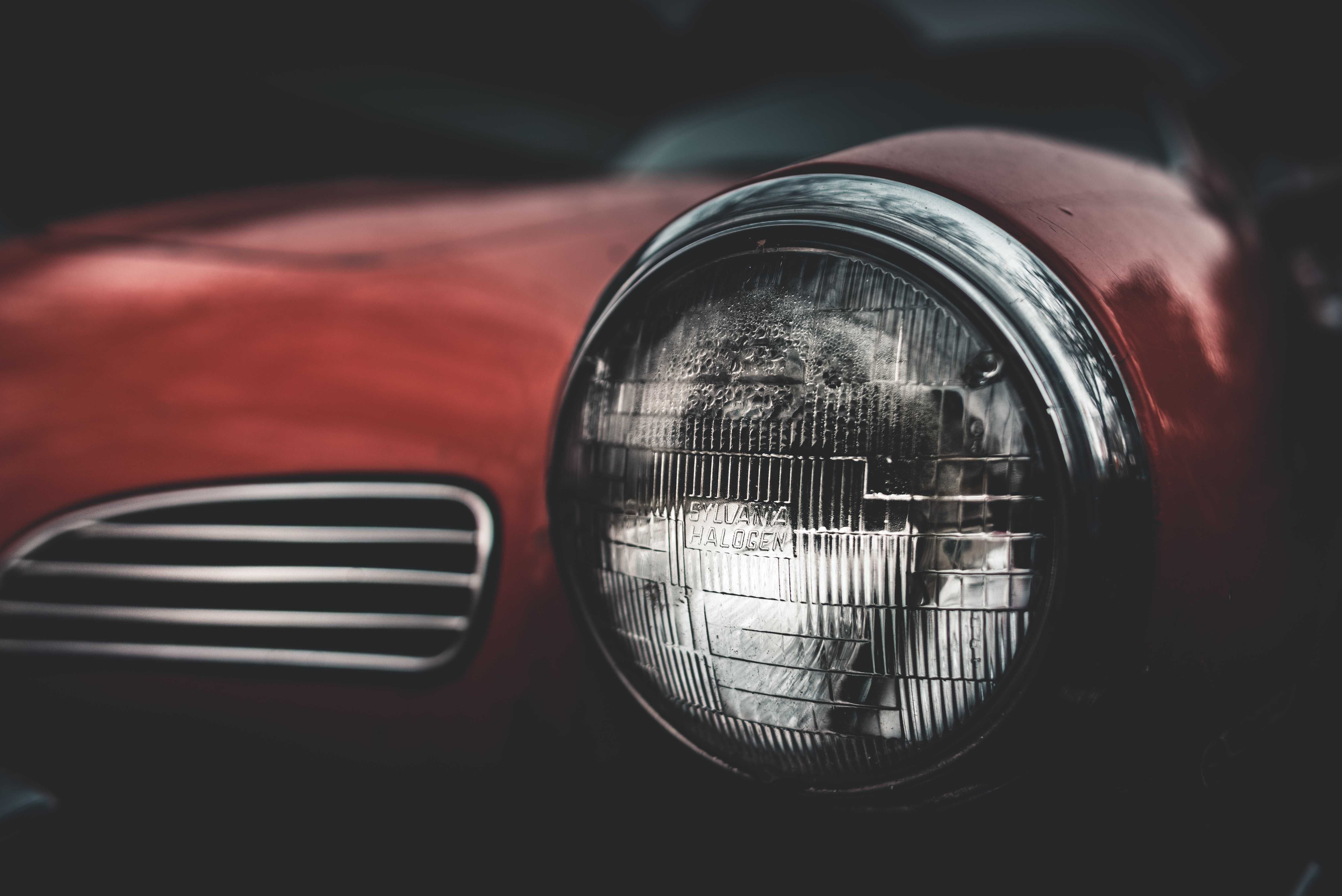 selective focus photography of red car headlight