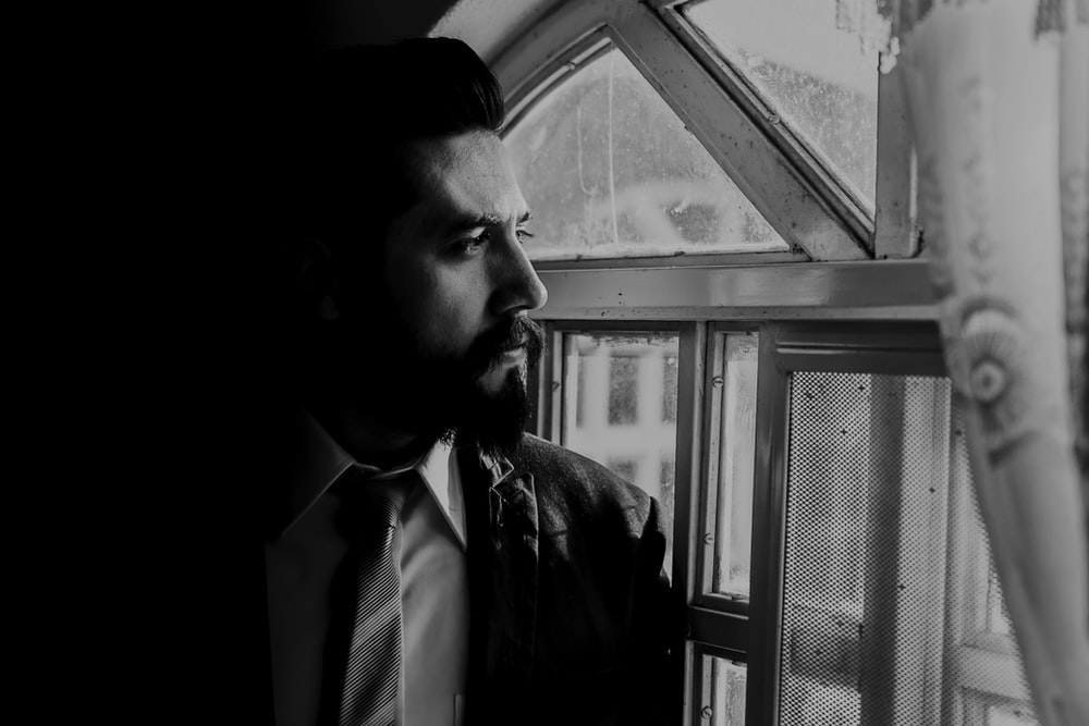 man in black suit looking out from window