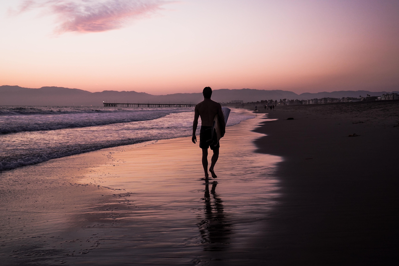 silhouette of man walking along seashore