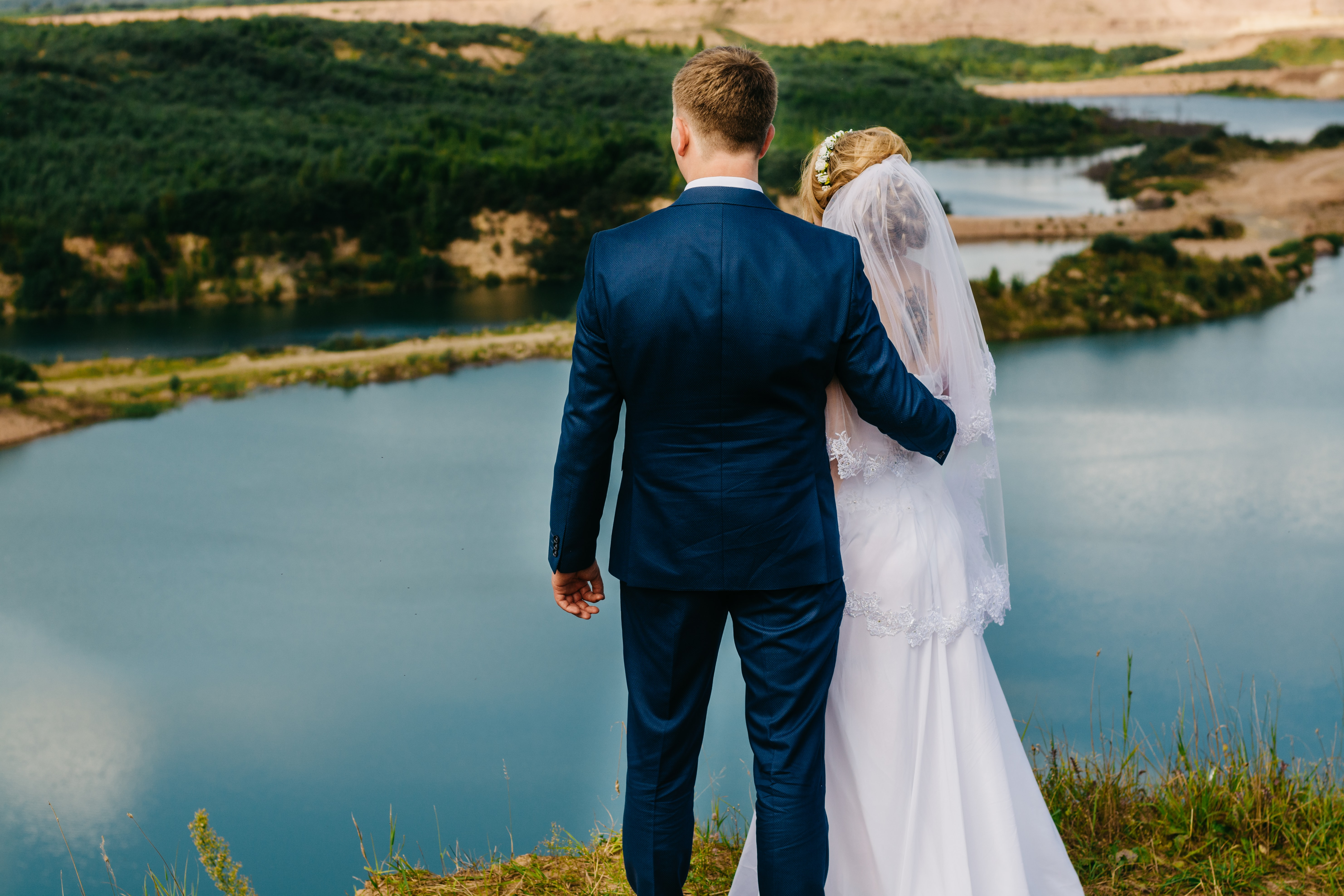 groom and bride standing on a cliff