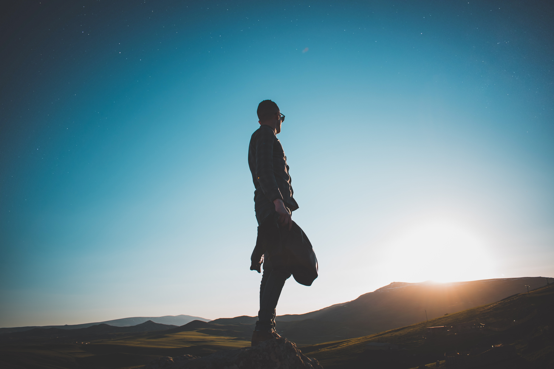 man standing on hill under blue sky