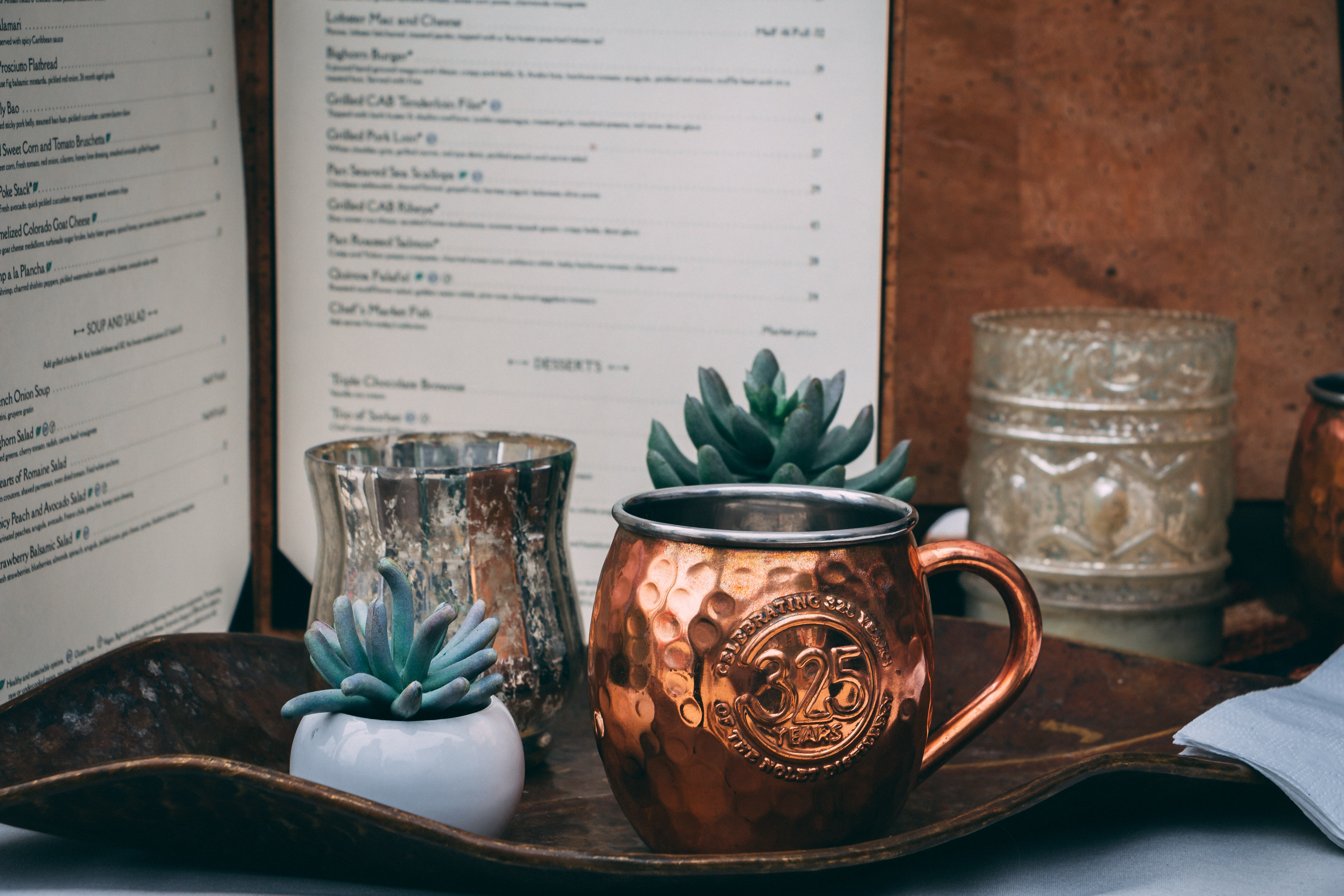 gold cup beside succulent plant on tray