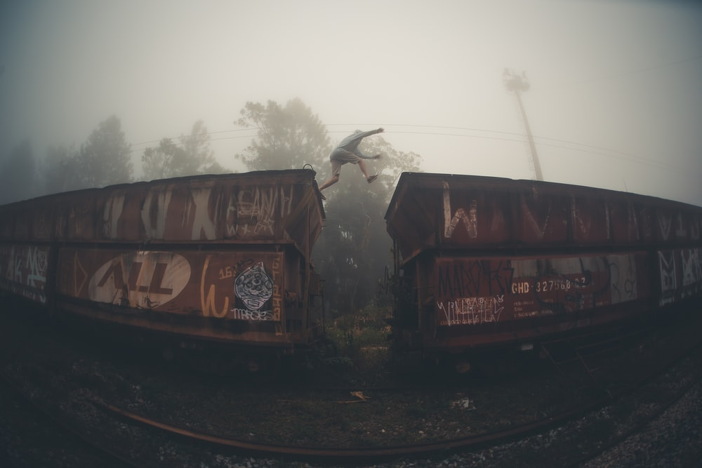 fisheye lens photography of man jumping from train cars