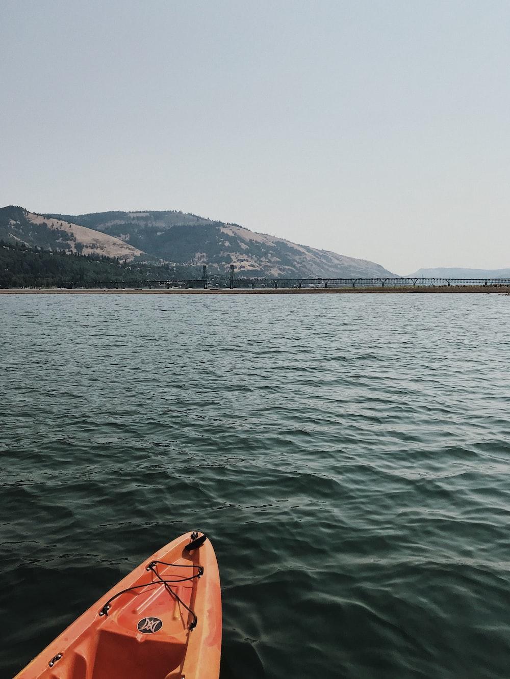 orange boat on body of water