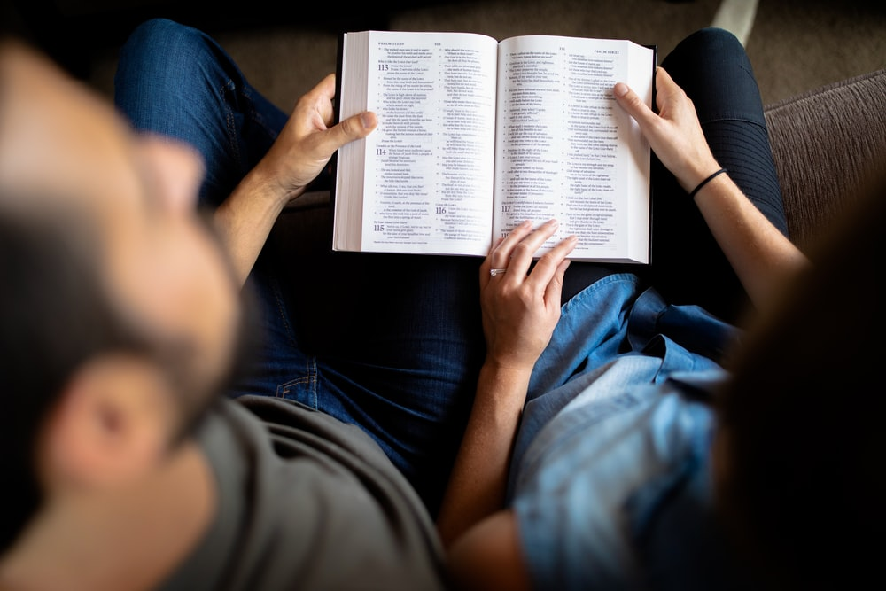couple reading book on couch