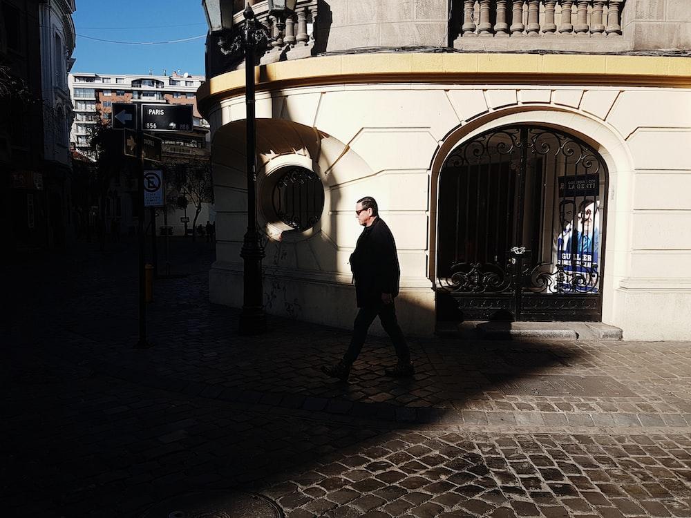 man walking near white concrete wall