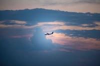 airplane in mid-air under cloudy skies