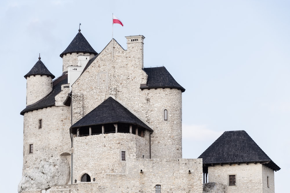 white and black castle with flag of Poland