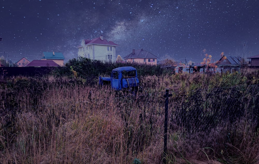 blue vehicle in grass field with houses at distance