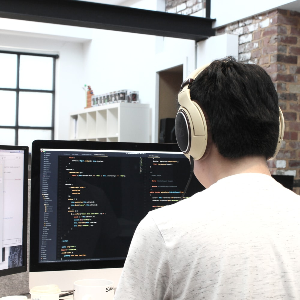man wearing headphones while using computer