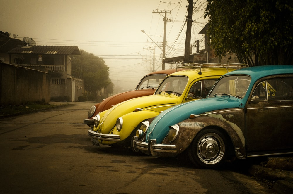 three assorted-color Volkswagen Beetle coups parked near houses