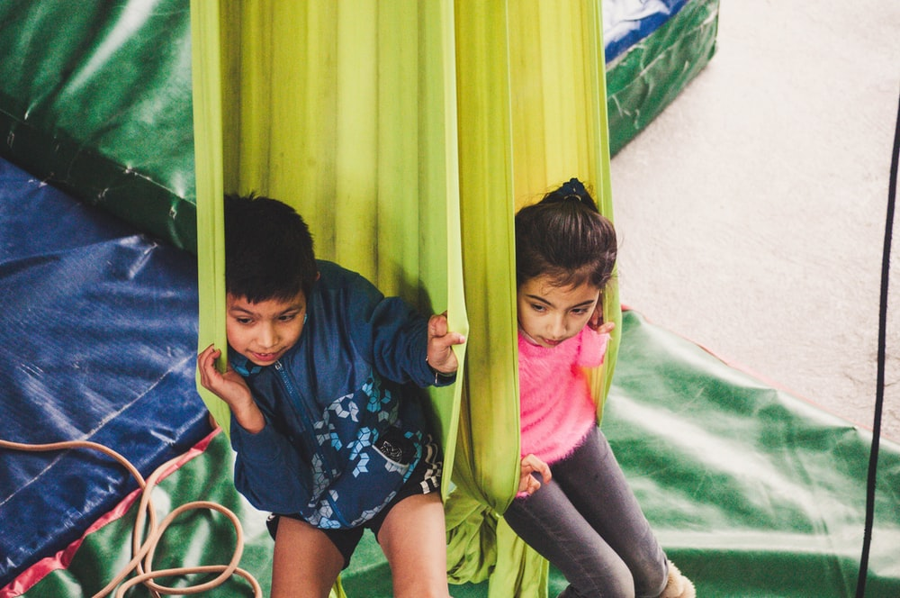 two kids playing on hammock