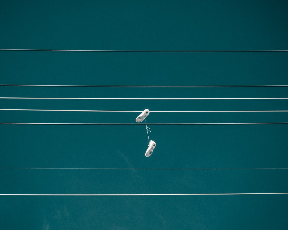 pair of white shoes hanging on cable