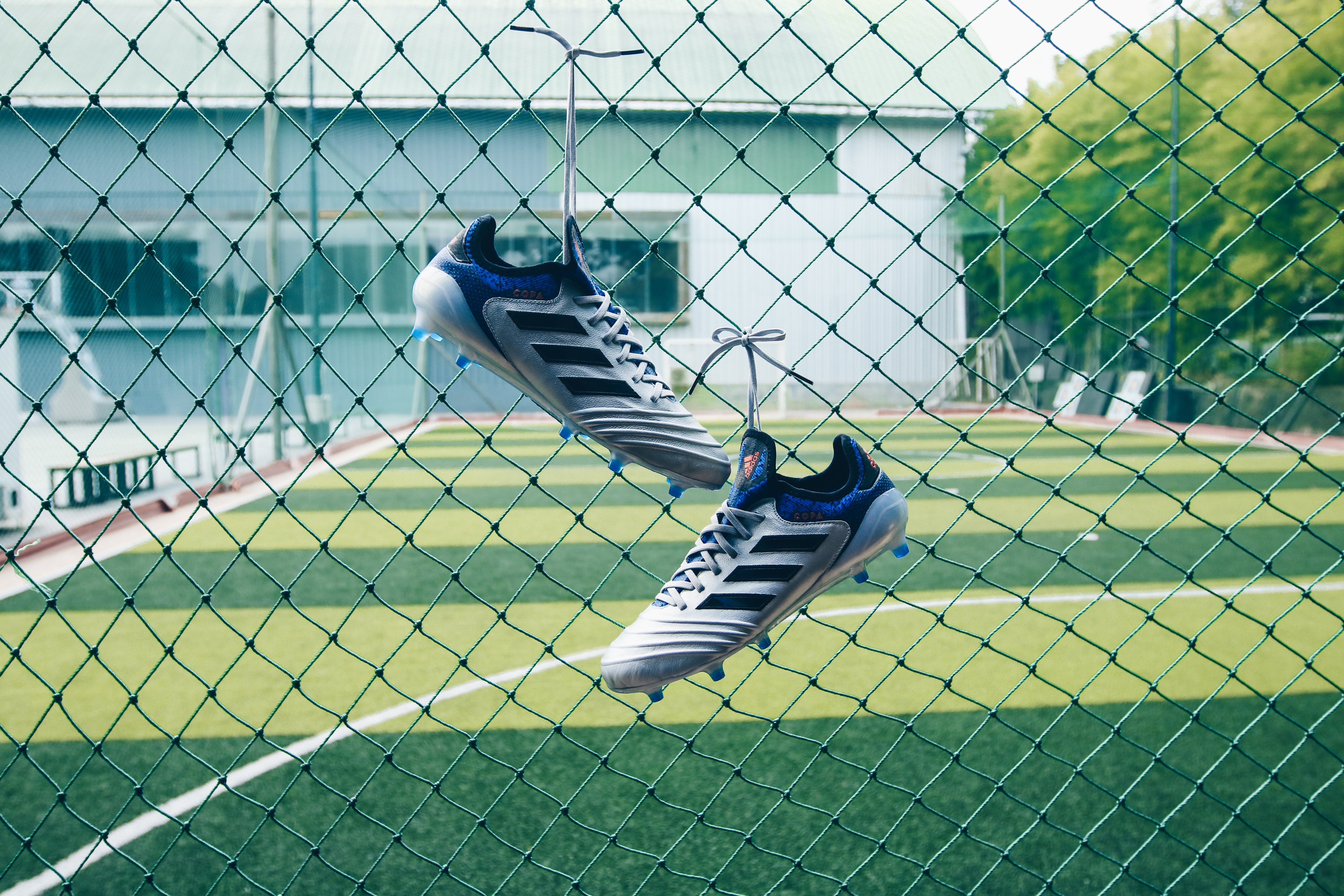 pair of soccer cleats on cyclone fence