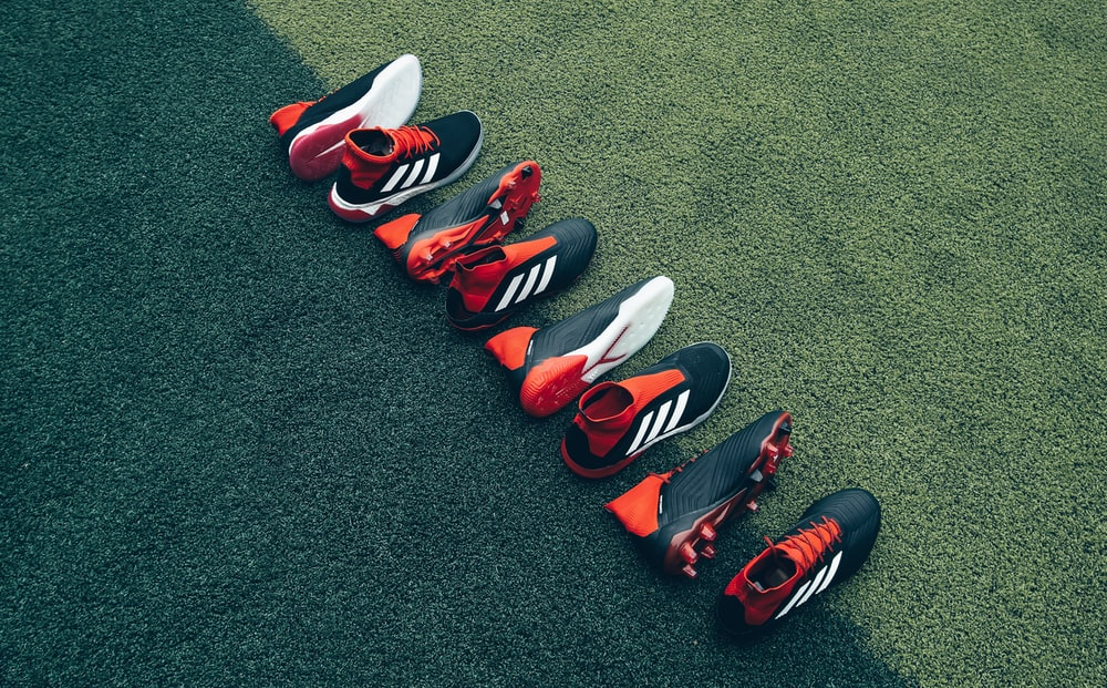 four pairs of black-and-orange shoes laid on green grass