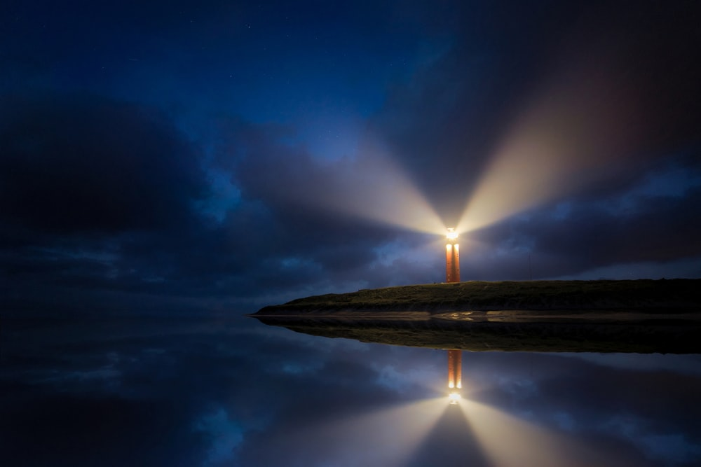 lighted brown lighthouse beside body of water
