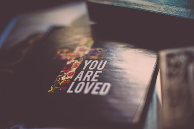 selective focus photography of you are loved book christian zoom background